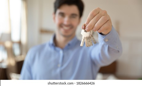 Mortgage lending. Smiling young man real estate agent or realtor giving you keys from purchased rented apartment, happy millennial customer client showing key of flat or house taken at loan or credit