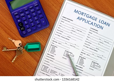Mortgage loan application with house key and calculator. Document about real estate business.