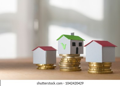 Mortgage and loan approved concept: paper houses on coin piles