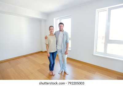 mortgage, moving, people and real estate concept - happy couple hugging at new home