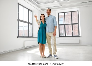 mortgage, people and real estate concept - happy couple with keys at empty room of new home