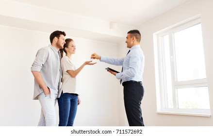mortgage, people and real estate concept - realtor giving keys to new apartment or home to happy couple