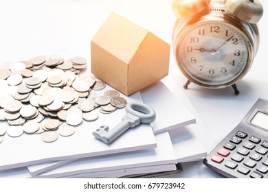 Mortgage, savings and finance concept for real estate property. House cardboard model, coins and key on document financial, isolated white background.
