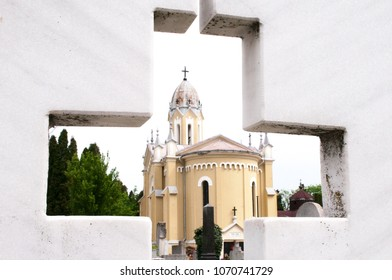 The mortuary chapel in a cemetery, seen through the mark of the cross cut in the marble plate.