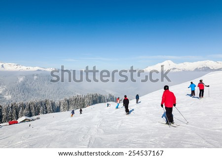 MORZINE, FRANCE - FEBRUARY 07, 2015: Skiers and snowboarders on La Combe piste in Morzine resort, part of the Portes du Soleil ski area.