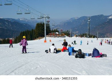 Morzine / France - March 18, 2015: Snowboarders sitting on the piste having a lesson with an instructor in the center of Morzine in the Portes du Soleil ski area of the French Alps.