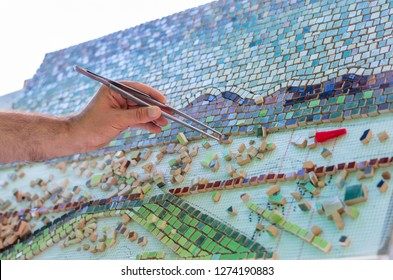 Mosaic as a ceramic or ceramic mosaic. The man organizes design with a tweezers a puzzle of ceramic elements for the construction of ceramic works. Artistic mosaics of terracotta.