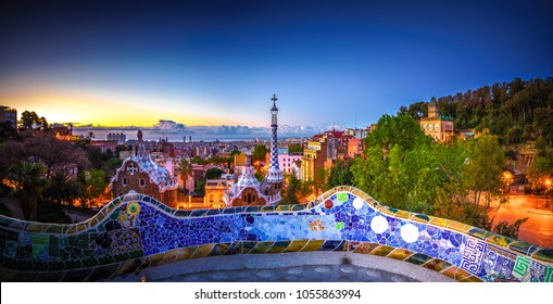 Mosaic tile panorama and Barcelona cityscape in famous park Guell at summer sunset,Spain