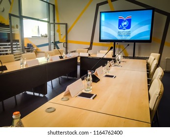 Moscow 1 July 2018: Meeting room with big table with microphones and huge TV screen. The boardroom table is set for the Annual General Meeting