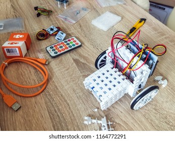 Moscow 1 July 2018: STEM or DIY Electronic Kit Robot assembly with robot engineer electronic. Electronic control kit DIY boards flat layout on wooden background.