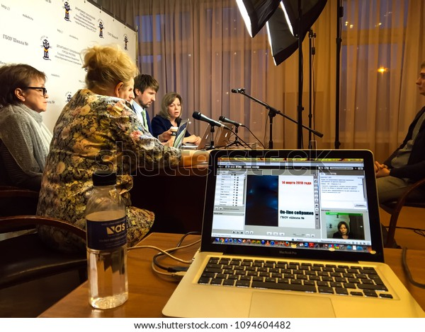 Moscow, 1 May 2018: Conducting a remote conference call. Teleconference - business people hand dialing a number on a modern conference mac book. Useful file for your annual report and other corporate