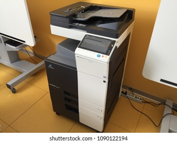 Moscow 1 May 2018: Professional multifunctional printer Konica Minolta on orange floor and wall background. Office printer accessories. Modern office equipment. Industrial technology concept