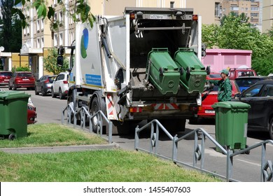 Moscow 12/06/2019 Garbage collection worker in residential area. Operating garbage truck used for rubbish disposal. Separate garbage collection problem, household waste recycling.