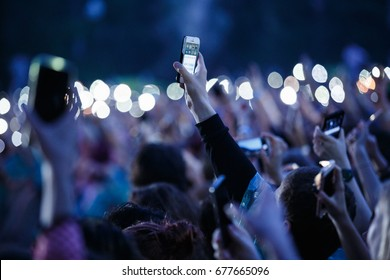 MOSCOW - 14 JULY,2017: Big crowd of music fans film concert with smart phone in hand.Music festival crowd filming open air entertainment event with smartphones.Bokeh background