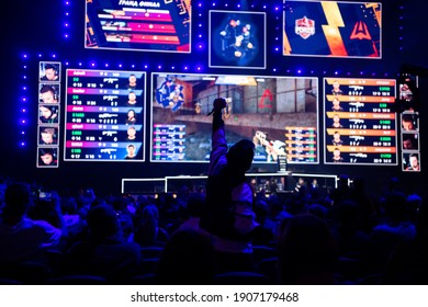 MOSCOW - 14th SEPTEMBER 2019: esports gaming event. Young man cheer for beloved gamers team at big arena during tournament game in front of a big screen.