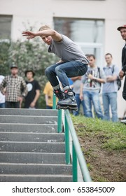 MOSCOW - 15 AUGUST,2015: Outdoor aggressive roller bladers competition  S3T contest.Young skater guy grinding handrail on skates.Dangerous extreme skating event.Roller grind rails