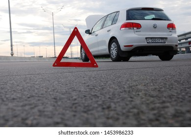 Moscow 15/07/2019 Car emergency or accident on highway road. White automobile with open bonnet waiting for roadside assistance. Red warning triangle in front of it, low angle