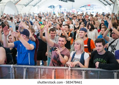 MOSCOW - 19 JUNE,2016:Concert audience enjoy big live music festival event.Music fans have fun at crowded dance floor.People put hands up in the air to the favourite musician play song