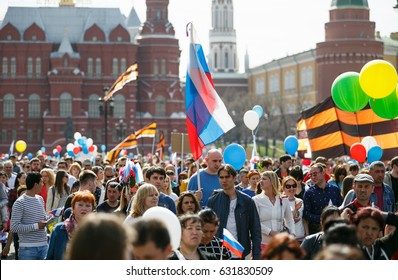 "MOSCOW - 1,MAY 2017: Big parade of working people on Red Square in Russia.Many people walk with national Russian flags & symbols to celebrate Labour Day.The main holiday theme is ""Peace.Labour.May"""