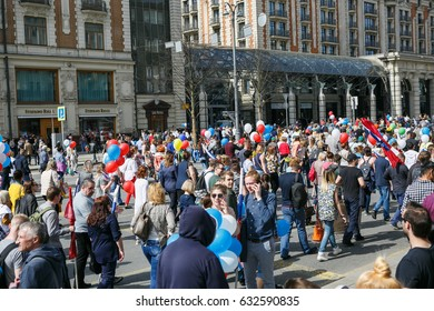 """MOSCOW - 1,MAY 2017: Big parade of working people on Red Square in Russia.Many people walk with national Russian flags & symbols to celebrate Labour Day.The main holiday theme is """"Peace.Labour.May"""""""