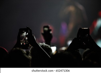 MOSCOW - 30 MARCH,2017: Music fans filming concert on mobile smartphones from the dance floor.Focus on guy touching the screen of mobile phone with camera on.Live show background