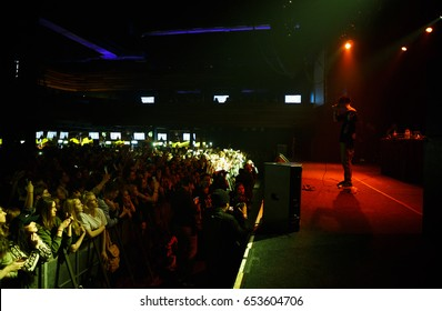 MOSCOW - 30 MARCH,2017: Rap singer Lil Peep sing on stage in front of the huge crowded dancefloor in the club.Concert audience have fun at the festival in nightclub