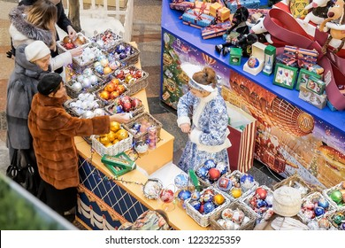 MOSCOW - 30 NOVEMBER, 2017: Female shop assistant dressed as Snow Maiden for Christmas sales wrapping beautiful handmade Christmas baubles in central shopping mall
