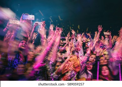 MOSCOW - 30 NOVEMBER,2016: Crowded dancefloor in night club.Full nightclub during musical concert show.People have fun.Entertainment event,fans enjoy music,wave hands.Double exposure effect