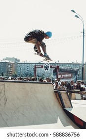 MOSCOW - 4 JULY,2015: Outdoor skate contest in Gorky Park.Big extreme sport competition for young skateboarders.Young skater jump high on mini ramp in skatepark.Air trick on skateboard