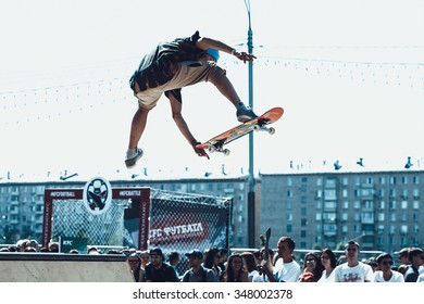 MOSCOW - 4 JULY,2015: Skateboarding contest event in outdoor skatepark.Skaters ride skateboard in skate park.Extreme sport skating competition in summer.Young skater boy jump air benihana grab trick