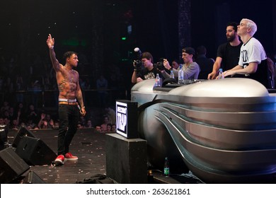 MOSCOW - 8 FEBRUARY,2015: Yellow Claw djs band playing live set in night club.Famous hip hop MC lead music show on stage in nightclub.Rap singer play music on scene.Cool tattoed black man rapper sing