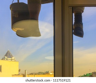 MOSCOW - APRIL 12, 2018: Washerman alpinist with bucket hangs behind office window against cityscape background on April 12, 2018 in Moscow.