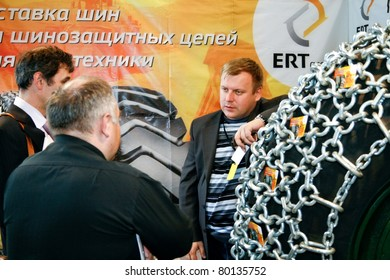 MOSCOW - APRIL 13: Men discuss tire with chain at the international exhibition of  the Mining and Processing of Metals and Minerals, MiningWorld on April 13, 2011 in Moscow