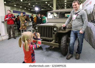 Moscow - April 15, 2016: A child photographs a man with a military jeep at the international exhibition of the fashion industry, Collection Premiere Moscow CPM. Public-event.