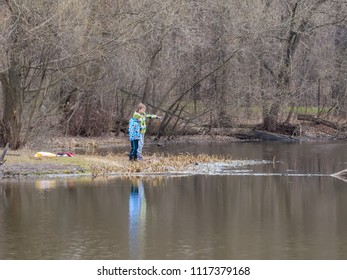 MOSCOW – APRIL 19, 2015: Fisher boys stands on lakeside against forest background on April 19, 2015 in Moscow.
