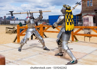 MOSCOW - APRIL 2016: Two armored fighters dressed as knights fight with axes at knight tournament reconstruction