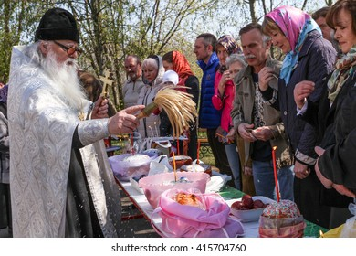 MOSCOW - APRIL 30, 2016: Orthodox priest spatter the holy water of Easter cakes at the celebration of Orthodox Easter by the church of St. Nicholas in Moscow.