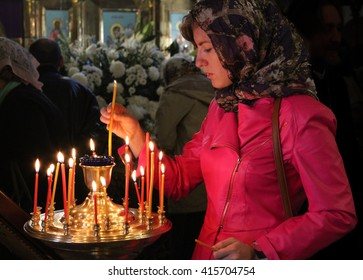 MOSCOW - APRIL 30, 2016: Unidentified woman light a candle at the celebration of Orthodox Easter by the church of St. Nicholas in Moscow.