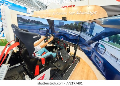 MOSCOW, AUG. 22, 2017: View on exhibition stand with 3d car driving simulator with wide led screens, electronic hydraulic tilting system. Man in car simulator chair. Car driving school game simulator