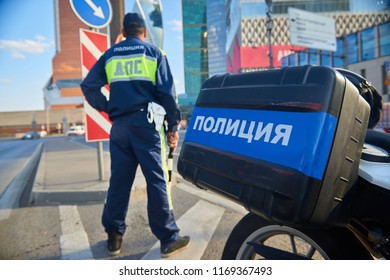 MOSCOW, AUG.29, 2018: Russian police motor cycle and armed police man monitors and controls road traffic in the background. and. Uniform and case text: Road Watch Police. POLICE