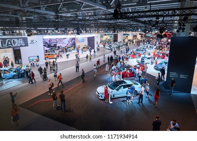 MOSCOW, AUG.31, 2018: Top panoramic view on latest cars of KIA, LADA and other car brands on automotive exhibition on MMAC 2018. People on automobile show of personal family cars