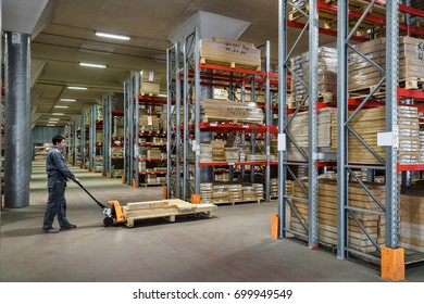 Moscow - August 1, 2017: The worker with fork pallet truck stacker works in storehouse. Logistics and transportation concept. People work inside modern storehouse. Panoramic view of warehouse interior