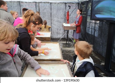 MOSCOW - AUGUST 18: Children participate master-class of sand animation from creative center 7bioz at festival Bright people in Gorky Park, on August 18, 2012 in Moscow, Russia.