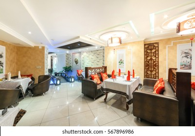 "MOSCOW - AUGUST 2014: Interior of Chinese cuisine restaurant ""HARBIN"" in the traditional style. Lounge with tables and leather couches with red pillows with Chinese characters"