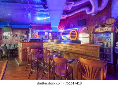 """MOSCOW - AUGUST 2014: Interior of the night club """"PIRAT"""". Bar counter in ship style with neon lights and bar stools"""