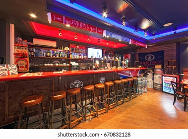 """MOSCOW - AUGUST 2014: The interior is traditional British pub """"Union Jack"""". Wooden bar with bar stools"""