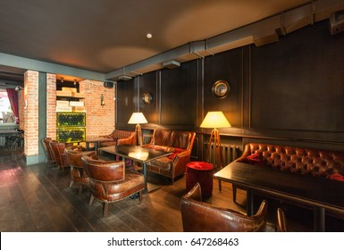 "MOSCOW - AUGUST 2014: The interior of the wine bar ""GAVROCH"". Tables with luxurious vintage armchairs and sofas"