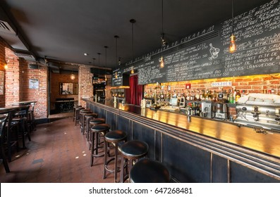 "MOSCOW - AUGUST 2014: The interior of the wine bar ""GAVROCH"". Long wooden bar counter with bar stools and a large menu on the slate board"