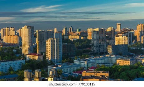 Moscow city bathed in yellow sun at dawn timelapse. Life in the stone jungle. An early foggy morning. Shadows moving on houses. Megalopolis aerial view from rooftop at Leninskiy avenue. The sky is