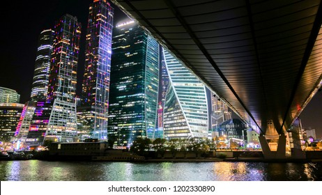 Moscow city business center illuminated view from under steel bridge tonight with river reflections